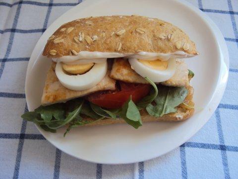 Sandwich de pollo, alioli de manzana, tomate, rúcula y huevo duro.